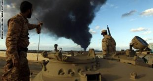 Members of the Libyan army stand on a tank as heavy black smoke rises from the city's port in the background after a fire broke out at a car tyre disposal plant during clashes against Islamist gunmen in the eastern Libyan city of Benghazi on December 23, 2014. Forces loyal to former general Khalifa Haftar and to internationally recognised Prime Minister Abdullah al-Thani have been battling for weeks against Islamists who have taken control of much of Libya's second city, and the capital Tripoli. AFP PHOTO / ABDULLAH DOMA        (Photo credit should read ABDULLAH DOMA/AFP/Getty Images)