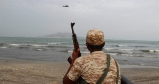 A Yemeni soldier looks on as a UAE military helicopter hovers over the sea off the southern city of Aden (Reuters/Fawaz Salman)